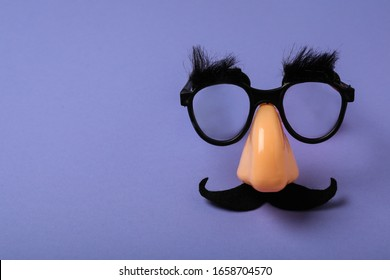 Funny party glasses on lilac background, space for text. April Fool's Day