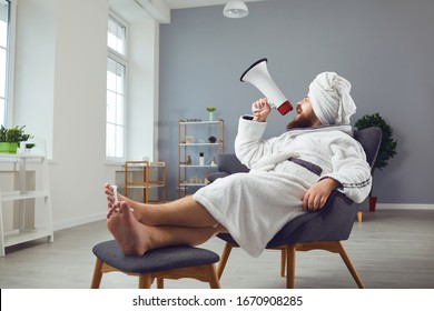 Funny pedicure beauty mask cosmetology concept. Funny fat man in a bathrobe shouts through a megaphone in room salon