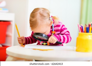 Funny photo of adorable toddler girl looking through magnifier