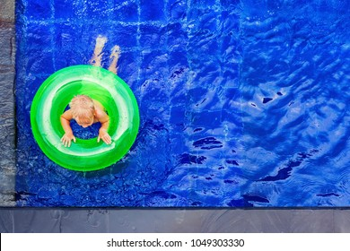 Funny photo of baby boy swimming with fun on inflatable swim ring in clear aqua park pool. Top view. Healthy family lifestyle, children with parents outdoor water sports activity on summer holidays.