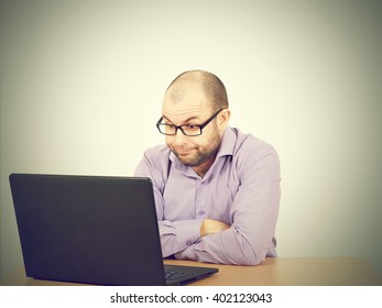 Funny photo of businessman bald with beard wearing shirt and glasses.  angry businessman working with laptop at table. Isolated on gray background