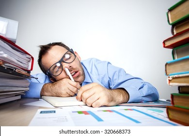 Funny photo of businessman with beard wearing shirt and glasses. Overworked businessman sleeping at table full of documents with pen in his nose. Isolated on white background