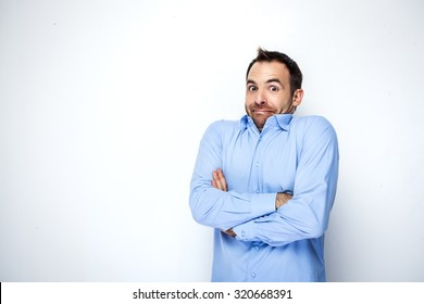 Funny photo of businessman with beard wearing shirt. Businessman looking at camera and shrugging his shoulders with discomfort. Isolated on white background