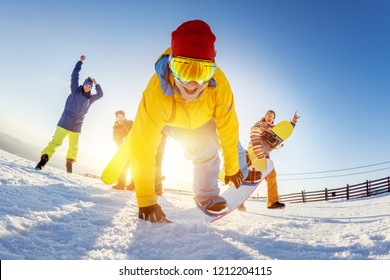 Funny photo with with friends at ski resort. Snowboarders are having fun in playful poses