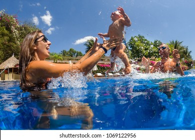 Funny photo of  happy active family young mother with active baby diving in swimming pool with fun jump .