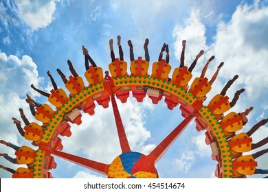Funny photo of legs of women, men in amusement park riding with fun on extreme attraction swinging upside down high in air on sky background. Family lifestyle, people activity on holiday with children
