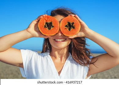 Funny photo of positive adult woman with smiling face holding in hands ripe fruit - orange papaya slices. Healthful food, low calories breakfast on sea beach Healthy lifestyle on summer family holiday