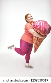 Funny picture of amusing, red haired, chubby woman on white background. Woman is holding a huge ice cream