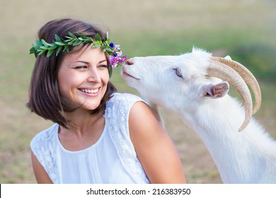 Funny picture a beautiful young girl farmer with a wreath on her head with white goat.