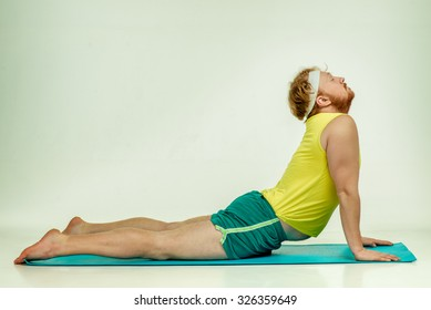 Funny picture of red haired, bearded, plump man on white background. Man wearing sportswear. Man is lying on the mat, he trains.
