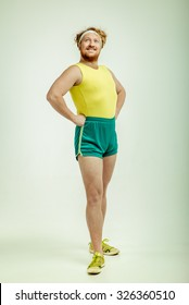Funny picture of red haired, bearded, plump man on white background. Man wearing sportswear