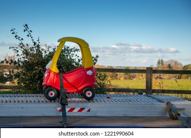 funny picture of small red toy car being delivered on an oversized large truck with English countryside in the background