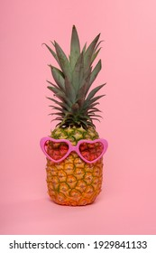 Funny pineapple with pink heart shaped glasses on a pink background