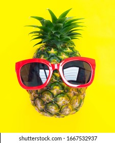 Funny pineapple in a red sunglasses over yellow background ,summer holiday concept