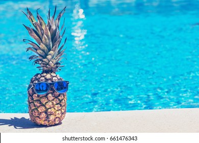 Funny pineapple in sunglasses near swimming pool.