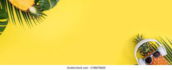 Funny pineapple wearing white headphone, listen music, isolated on yellow background with tropical palm leaves, top view, flat lay design concept.