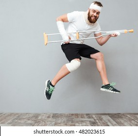 Funny plauful young man jumping and having fun with crutch over white background