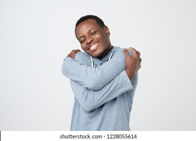 Funny playful african guy cuddling himself and smiling from pleasure, closing eyes and dreaming about finding soulmate