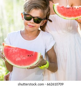 Funny playful boy eating watermelon wearing sunglasses standing near mother, outdoors portrait on a sunny summer day