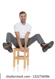 funny playful casual man celebrates while sitting on a chair with legs in the air on white background