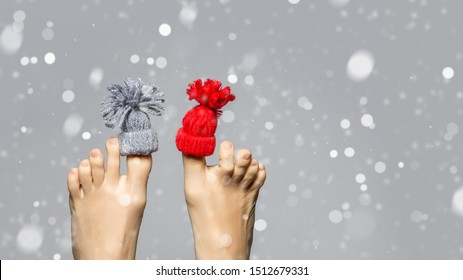 Funny playful female feet over grey snow background. Winter care concept