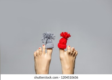 Funny playful female feet with small knitted hat on big fingers