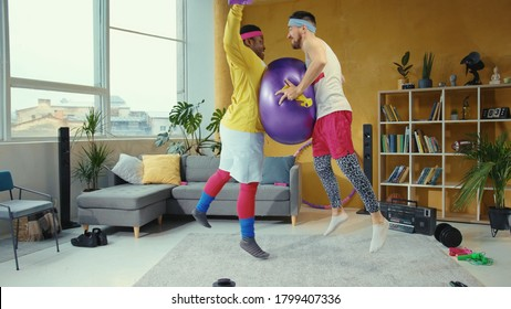 Funny playful unfit young retro styled men playing with fitness ball jumping and fighting in the living room. Concept of fun, competition, humor in sports.