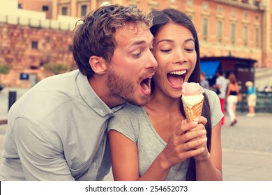 Funny playful young couple eating ice cream. Goofy portrait of boyfriend teasing girlfriend biting off a cold dessert in city summer, Stockholm, Sweden, Europe.