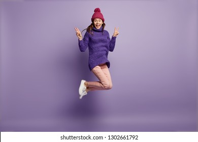 Funny pleased overjoyed woman makes peace sign with both hands, jumps over bright purple background, has fun indoor, exclaims loudly, celebrates something, feels pleasure, wears winter clothes