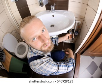 Funny plumber repairing sink pipes in bathroom, close up view