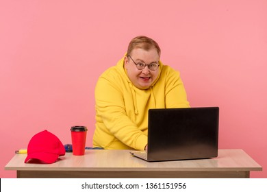 Funny plump man geek in yellow sweatshirt having foolish face expression using laptop with funny freak grimace