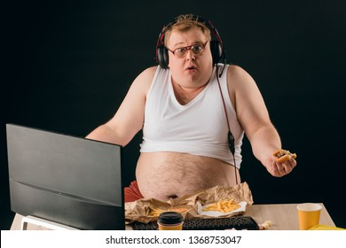 funny plump man holding a burger and looking at the camera with astonished , amazed expression . close up portrait. How do you lose weight Why I am fat