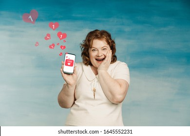 Funny plump woman with red hair hollowly holds the phone. Lots of likes per post.
