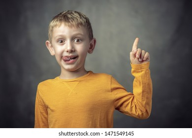 Funny portrait of a 6 year old Caucasian child with his tongue sticking out. shot taken in the studio.