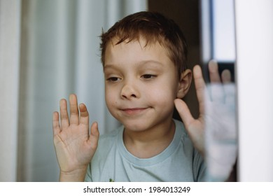 funny portrait of adorable caucasian 6-7 years old boy sticking to the window  and  looking outside. Staying home because cold and flu. Image with selective focus