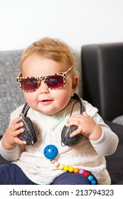 Funny portrait of a baby with headphones and sunglasses
