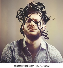 Funny portrait of bearded man with analog film over his head