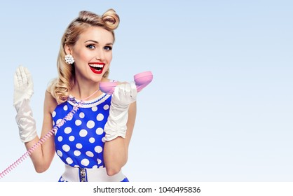 Funny portrait of beautiful happy woman with phone, dressed in pin-up style dress in polka dot and white gloves, with copyspace area for slogan or advertising text message, on blue background.