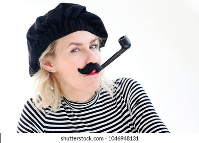 funny portrait of blond woman as french man with beret, mustache and pipe