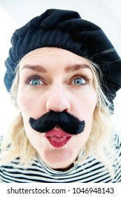 funny portrait of blond woman as french man with beret and mustache blowing a kiss