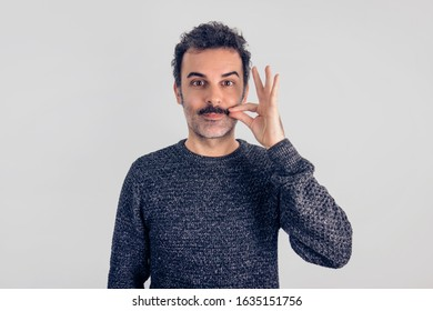 Funny portrait of brown, smiling, handsome man touching his mustache with gray sweater. Gray background.