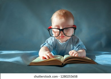 Funny portrait of cute baby in glasses. The baby lies on his stomach and reads an old book on a blue background.