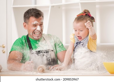 Funny portrait of cute little daughter with handsome father cooking pastry, working with rolling pin and throwing flour. Dirty aprons
