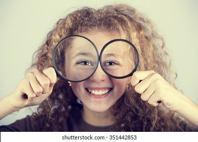 Funny portrait of cute little girl looking through  magnifying glass.Curious Smiling little girl looking through magnifying glass over white background.