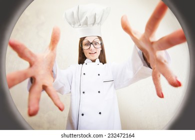 Funny portrait of a female chef reaching for the saucepan, view from below