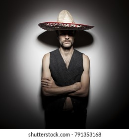 Funny portrait of frowning mexican criminal man with folded arms and sombrero hat