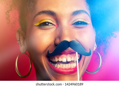 funny portrait of a girl with curly hair and a cardboard mustache on a stick. close-up portrait in colored light and with light rays