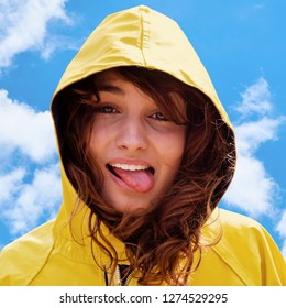 Funny portrait of a girl in yellow raincoat