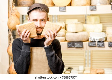 Funny portrait of a handsome cheese seller in uniform standing with seasoned cheese in front of the store showcase full of different cheeses