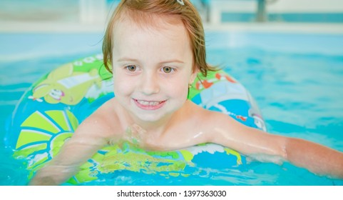 Funny portrait of happy cute little child girl playing with colorful ring in swimming pool.